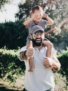 man with kid on shoulders