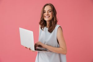Image of cheerful young woman standing isolated over pink background using laptop computer. Looking camera.