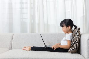 Happy Asian Chinese little girl lying on the sofa with laptop in the living room at home.